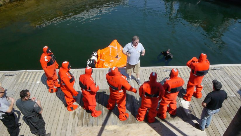 Fishermen in orange survival suits at a training class.