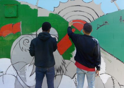 Two teens painting a mural.